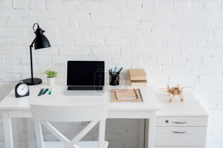 work desk with laptop at home in front of white brick wall