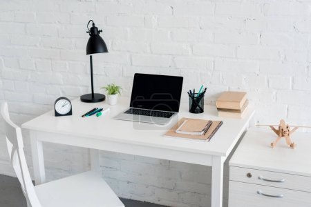 Photo for Modern workplace with laptop at home in front of white brick wall - Royalty Free Image