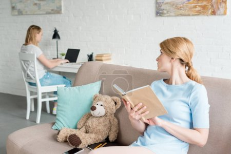 mother reading book and sitting on couch while her daughter working with laptop