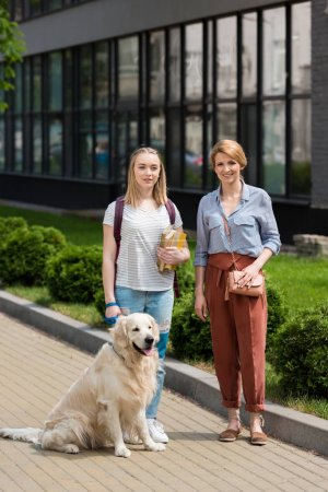 mother and teen daughter standing on street with their golden retriever