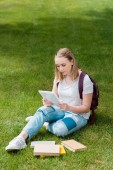 teen student girl using tablet while sitting on grass in garden
