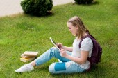 teen student girl using tablet while sitting on grass
