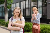disappointed teen daughter with books looking down while her mother smoking cigarette blurred on background