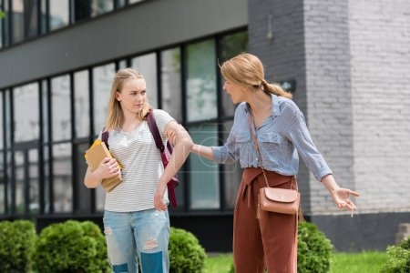 mother pulling her daughter and forcing to go somewhere while she holding stack of books