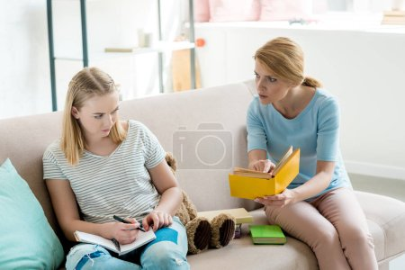 angry mother doing homework together with daughter