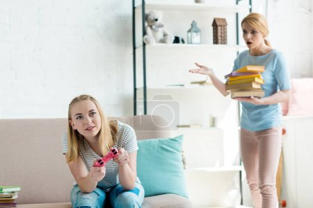 mother with stack of books forcing her daughter to study while she sitting on couch and playing console game