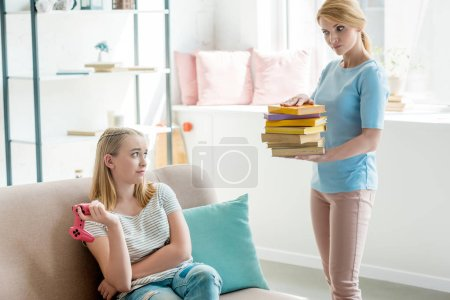 Photo for Mother with stack of books forcing her daughter to study while she sitting on couch with gamepad - Royalty Free Image