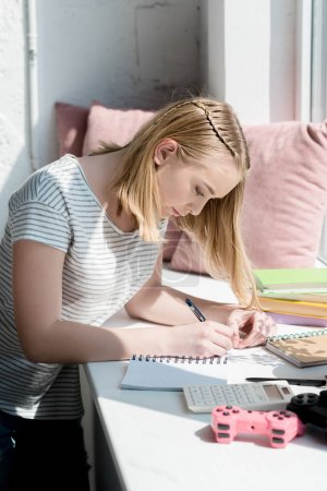 side view of focused teen student girl doing homework