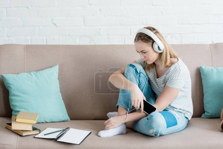sad teen girl sitting on couch and listening music with headphones