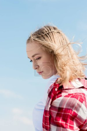 thoughtful teen girl with hair waving on wind in front of blue sky