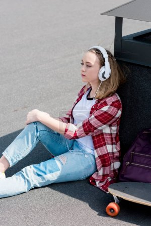 beautiful teen girl with skateboard sitting on rooftop and listening music with headphones