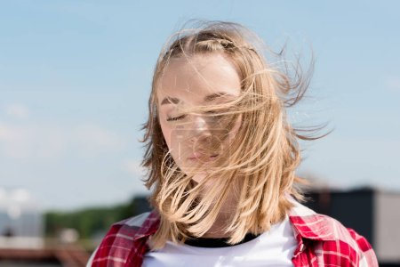 beautiful teen girl with hair waving on wind in front of blue sky