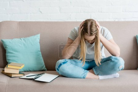 Photo for Depressed teen girl sitting on couch with books and holding head - Royalty Free Image
