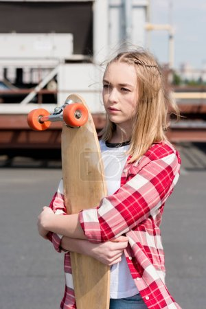 beautiful teen girl in red plaid shirt embracing skateboard on rooftop