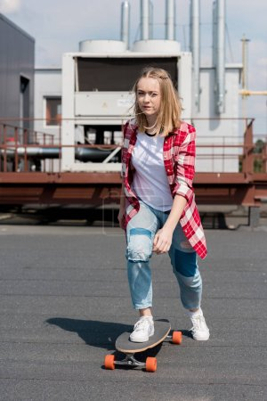 active teen girl riding skateboard on rooftop