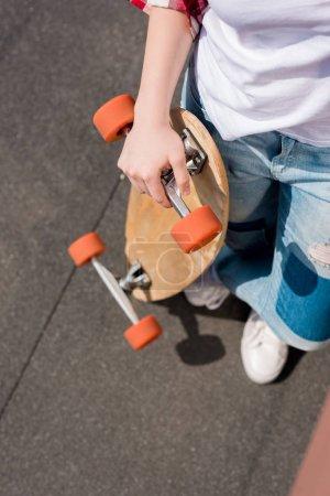 cropped shot of teen girl holding skateboard