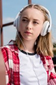 close-up portrait of teen girl in red plaid shirt and headphones