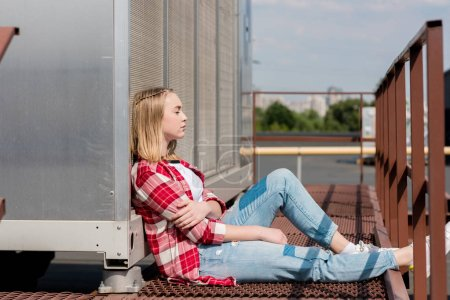 side view of thoughtful teen girl in red plaid shirt sitting on rooftop