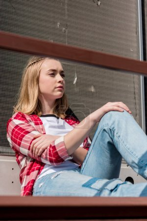 thoughtful teen girl in red plaid shirt sitting on rooftop