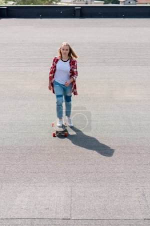 high angle view of teen girl riding skateboard on rooftop