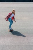 high angle view of active teen girl riding skateboard on rooftop
