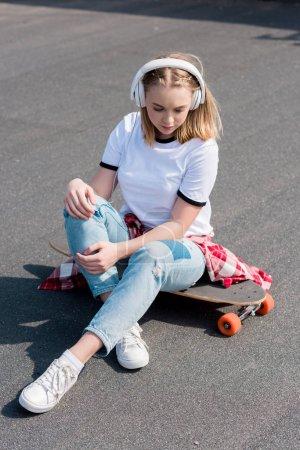stylish teen girl listening music in headphones while sitting on skateboard