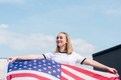 smiling teen girl with usa flag in front of blue sky