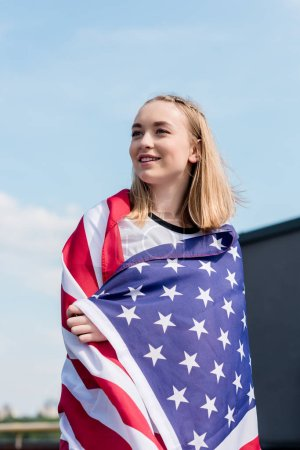 beautiful teen girl covered with usa flag in front of blue sky