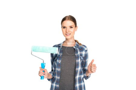 smiling young woman doing thumb up gesture and holding paint roller isolated on white background