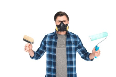 man in respirator holding paint brush and paint roller isolated on white background