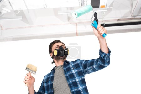 low angle view of man in respirator working by paint roller and paint brush