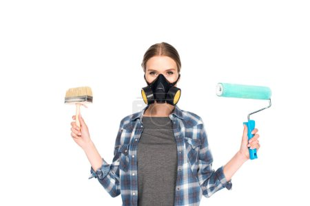 woman in respirator holding paint brush and paint roller isolated on white background