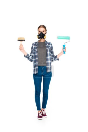 young woman in respirator holding paint brush and paint roller isolated on white background