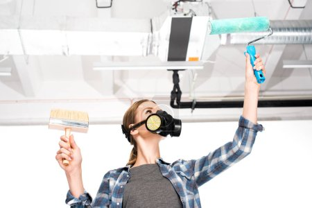 low angle view of woman in respirator holding paint roller and paint brush with pipes on behind