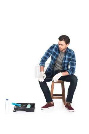 man in protective gloves resting on chair near roller tray and paint roller isolated on white background