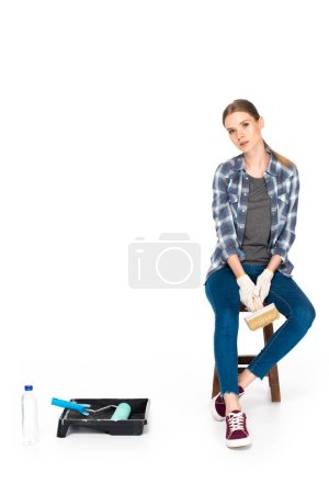 young woman sitting on chair with paint brush near bottle, roller tray and paint roller isolated on white background