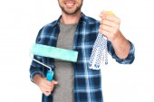 cropped image of man holding protective gloves and paint roller isolated on white background