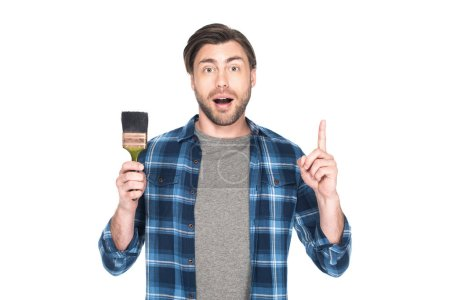 surprised young man with paint brush doing idea gesture isolated on white background