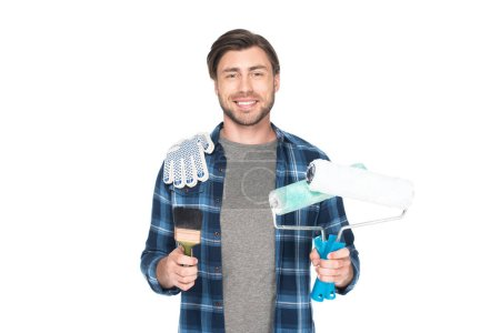 smiling man with paint rollers, protective gloves and paint brush isolated on white background