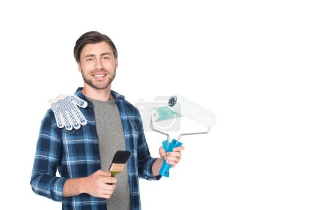 young smiling man with paint rollers, protective gloves and paint brush isolated on white background
