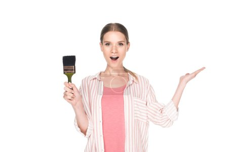 surprised woman holding paint brush isolated on white background