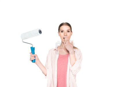young woman closing mouth by palm and holding paint roller isolated on white background