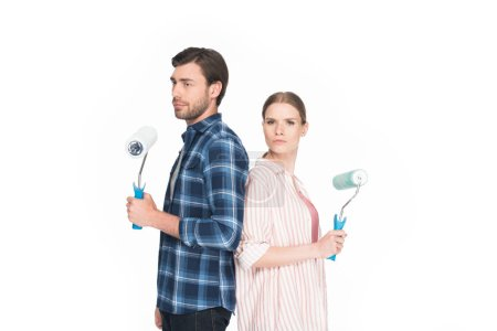 Photo for Young couple with paint rollers standing back to back isolated on white background - Royalty Free Image