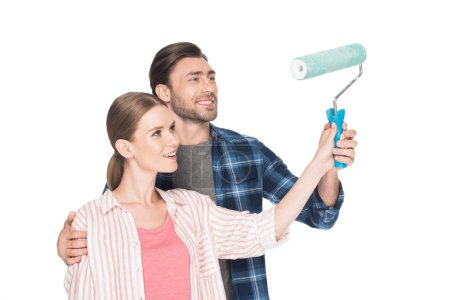 smiling man teaching girlfriend painting by paint roller isolated on white background