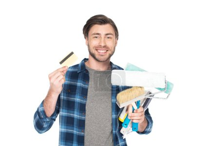 smiling man with credit card holding paint rollers and paint brush isolated on white background