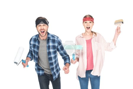 happy screaming couple in headbands with paint rollers and paint brush isolated on white background
