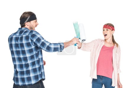 young screaming man fighting with girlfriend by paint rollers isolated on white background