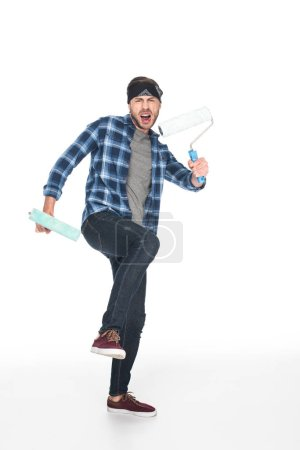 angry screaming man in headband holding paint rollers isolated on white background