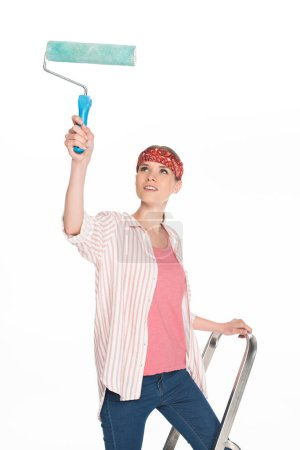 young woman in headband standing on ladder and painting by paint roller isolated on white background