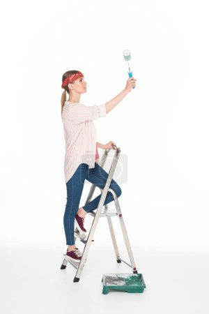 side view of woman in headband standing on ladder and painting by paint roller isolated on white background